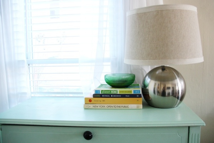 Books and lamp on blue dresser.
