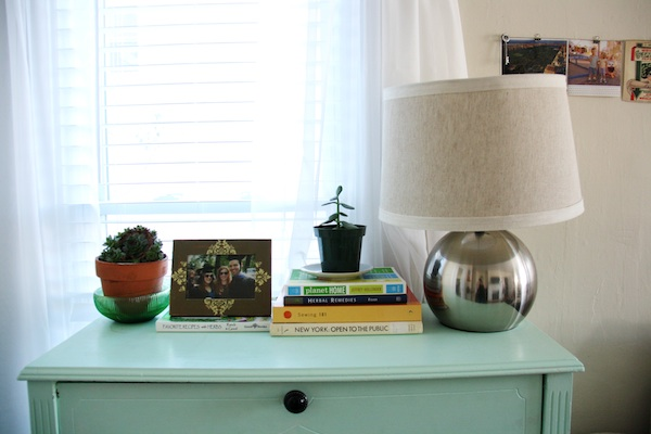 Plants and books on blue dresser.